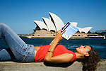 A woman reads a guidebook on Sydney harbour opposite the Opera House.  Sydney, New South Wales, AUSTRALIA.