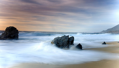 A SLOW EXPOSURE OF THE WAVES AT GARRAPATA STATE BEACH AT SUNSET ALONG THE BIG SUR COASTLINE IN CALIFORNIA