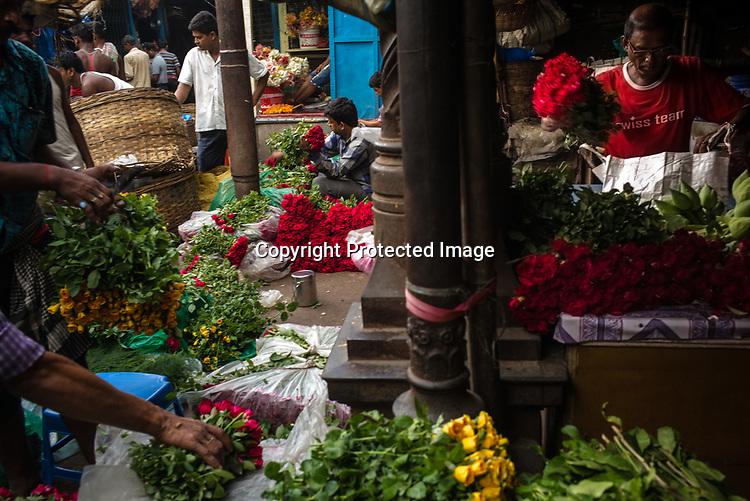 Vendors pack flowers for customers at the Mullik Ghat Flower market in Howrah, Kolkata, West Bengal  on Friday, May 26, 2017. Photographer: Sanjit Das