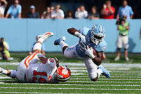 CHAPEL HILL, NC - SEPTEMBER 28: Javonte Williams #25 of the University of North Carolina is tackled by Tanner Muse #19 of Clemson University during a game between Clemson University and University of North Carolina at Kenan Memorial Stadium on September 28, 2019 in Chapel Hill, North Carolina.