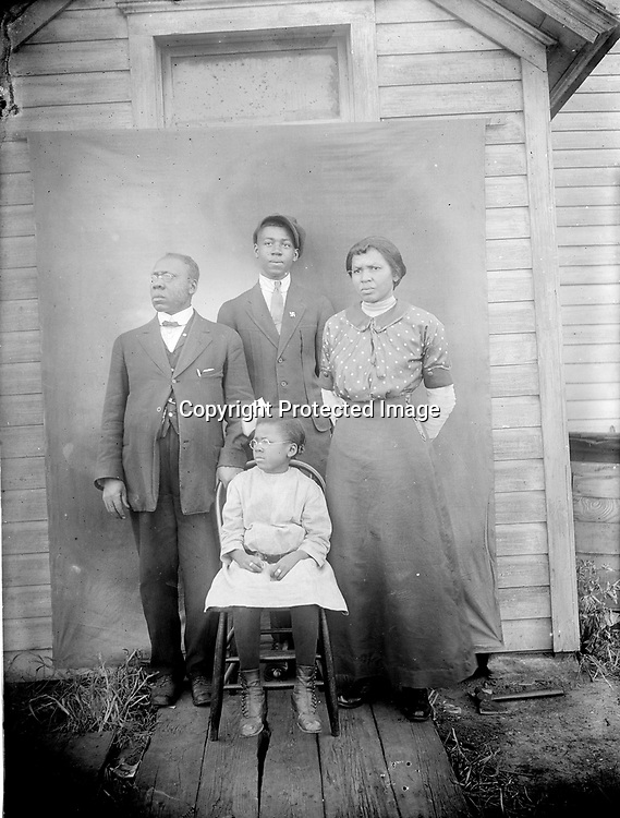 THE TALBERT FAMILY. Rev. Albert W. Talbert (1859-?), his wife Mildred (1874-1960), son Dakota (1898-1968), and daughter Ruth (1906-2005) pose in front of Newman Methodist Episcopal Church at 733 J Street around 1914. The Talberts came to Lincoln in 1914 from Guthrie, Oklahoma, and Reverend Talbert ministered to his African American congregation until 1920. Mother Millie later worked as a hairdresser to support Ruth through Lincoln High School and as she earned a two-year teaching certification at the University of Nebraska in 1926. This image is pivotal in the understanding of this body of photographs, because the negative reached California in the collection of Douglas Keister, while an original print of the family portrait survived in the possession of Ruth Talbert (later Greene, then Folley). She told Abigail Anderson and Edward F. Zimmer in 2002, &quot;Mr. Johnny Johnson took our picture.&quot; Her oral history interviews with Anderson greatly enriched Lincoln history and this book.<br /> <br /> Photographs taken on black and white glass negatives by African American photographer(s) John Johnson and Earl McWilliams from 1910 to 1925 in Lincoln, Nebraska. Douglas Keister has 280 5x7 glass negatives taken by these photographers. Larger scans available on request.