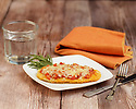 Grilled breaded chicken breast served on a white plate with melted cheese, tomato marinara sauce, and sprig of rosemary
