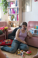 Mom surrounded by toys taking a telephone break age 28. Balucki District Lodz Central Poland