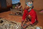 A woman in the central highlands of Madagascar stacks wild silk cocoons in preparation for boiling as one of the first steps to create traditional silk weavings, while a woman behind her creates spools of raw silk yarn.