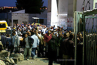 "Palestinian workers lined up next to the Separating Wall in Bethlehem as they wait to cross the ""Gilo Terminal"" in order to work in Jerusalem. According to UNRWA thousands workers cross the Gilo Terminal from all Southern West Bank. With the economic crises in the West Bank, workers try to get permits and take the long journey to work in Israel. Next week Pope Benedict XVI will visit Bethlehem. Photo by Quique Kierszenbaum"