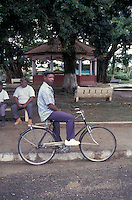 Black gentleman sitting on a bicycle in front of the main sqaure in the town of Bocas del Toro, Isla Colon, Panama