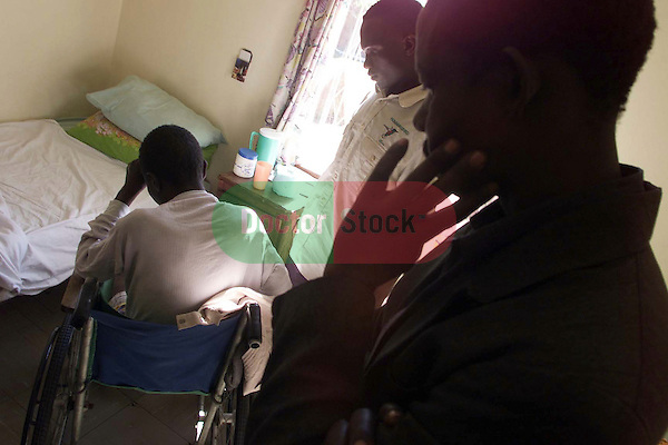 NOT MODEL RELEASED; FOR EDITORIAL USE ONLY... African man suffering with HIV Aids sitting in wheelchair at Mashambanzou Care Trust run by nuns, in Harare, Zimbabwe, while family members stand in worry