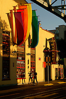 Couple walking under colorful banners at sunset, Granville Island, Vancouver, British Columbia, Canada