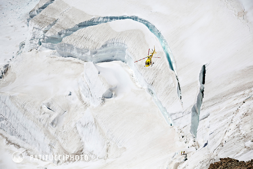 A helicopter flying over the south face of the Mönch after dropping off two rescue team personel at the scene of a fatal climbing mountaineering accident
