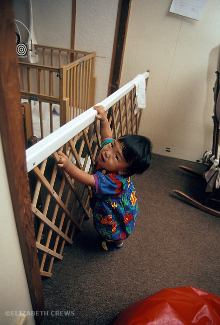 Berkeley CA Child, around age one, at safety barrier at day care  MR