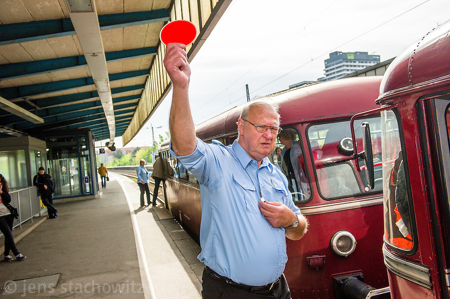 Conductor giving the 	enable signal for the departure of the railbus. | Der Schaffner gibt die Fahrt für den Schienbus frei.