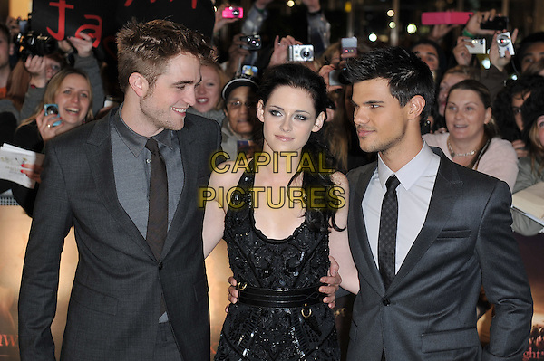 Robert Pattinson, Kristen Stewart and Taylor Lautner.'The Twilight Saga: Breaking Dawn - Part 1' UK film premiere at Westfield Stratford City, London, England..16th November 2011.half length rob grey gray suit jacket black dress belt sequins sequined couple arm around waist stubble facial hair profile halterneck .CAP/MAR.© Martin Harris/Capital Pictures.