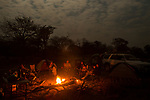 African Lion (Panthera leo) trackers, Christopher Muduwa and Timbo Frackson, and biologists, Jake Overton, Luke Hunter, Xia Stevens, and Kim Young-Overton, sitting around camp fire at night, Kafue National Park, Zambia