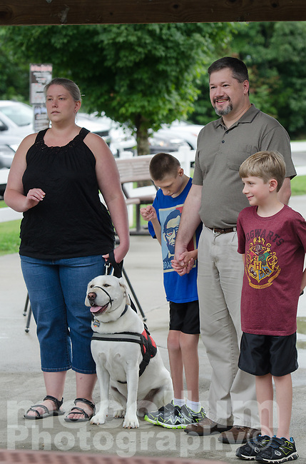"Michael McCollum<br /> 8/2/18<br /> The Overman family (left to right) mom Marie, Ryan,13, dad David and Alex,7. (along with Ryan's service dog ""Shadow"") at the reveal ceremony where it was announced to 13 year old Ryan Overman of west Knoxville that The Wish Connection is granting Ryan's wish to go to Washington DC and visit the White House at Carl Cowan Park, 10058 S Northshore Dr, Knoxville, TN , Thursday, August 2, 2018 at 5:45pm. Approximately 50-60 people attended, including the Overman family, friends, and AT&T Employees. The Bearden High School Cadets also attended and lead the pledge of allegiance.<br />  The AT&T Wish Connection is going to send Ryan, his family, and his service dog to Washington DC and while they are gone, the group of volunteers will be doing a makeover on his bedroom and turn it into the ""Oval Office"" at the White House.<br /> Ryan was born two weeks prematurely on May 13, 2005.  During the pregnancy he was classified as high risk due to a measured lack of growth and, after a brief stay in the hospital, he came home weighing only 4 lbs 5 oz.  His development was much slower compared to his peers, such as not learning to walk until he was well over a year old, and he was much smaller. The Overman family worked with Tennessee Early Intervention Services (TEIS) when Ryan was about one year old and with their help they were able to get Ryan enrolled through TEIS to receive Occupational, Physical, and Speech Therapy.  When Ryan turned three he transitioned from TEIS to the Knox County Early Intervention Program and began attending a special school to continue his therapies until he was old enough to enroll at Cedar Bluff Elementary and now is at Cedar Bluff Middle School. In 2016, Ryan was diagnosed to have retinitis pigmentosa, a degenerative disease of the retinas that under the best of circumstances causes severe tunnel vision, but more commonly results in complete blindness.<br />  Despite the physical difficulties that Ryan has had to endure over the l"