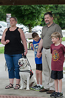 Michael McCollum<br /> 8/2/18<br /> The Overman family (left to right) mom Marie, Ryan,13, dad David and Alex,7. (along with Ryan&rsquo;s service dog &ldquo;Shadow&rdquo;) at the reveal ceremony where it was announced to 13 year old Ryan Overman of west Knoxville that The Wish Connection is granting Ryan&rsquo;s wish to go to Washington DC and visit the White House at Carl Cowan Park, 10058 S Northshore Dr, Knoxville, TN&nbsp;, Thursday, August 2, 2018 at 5:45pm. Approximately 50-60 people attended, including the Overman family, friends, and AT&amp;T Employees. The Bearden High School Cadets also attended and lead the pledge of allegiance.<br /> &nbsp;The AT&amp;T Wish Connection is going to send Ryan, his family, and his service dog to Washington DC and while they are gone, the group of volunteers will be doing a makeover on his bedroom and turn it into the &quot;Oval Office&quot; at the White House.<br /> Ryan was born two weeks prematurely on May 13, 2005.&nbsp; During the pregnancy he was classified as high risk due to a measured lack of growth and, after a brief stay in the hospital, he came home weighing only 4 lbs 5 oz.&nbsp; His development was much slower compared to his peers, such as not learning to walk until he was well over a year old, and he was much smaller. The Overman family worked with Tennessee Early Intervention Services (TEIS) when Ryan was about one year old and with their help they were able to get Ryan enrolled through TEIS to receive Occupational, Physical, and Speech Therapy.&nbsp; When Ryan turned three he transitioned from TEIS to the Knox County Early Intervention Program and began attending a special school to continue his therapies until he was old enough to enroll at Cedar Bluff Elementary and now is at Cedar Bluff Middle School. In 2016, Ryan was diagnosed to have retinitis pigmentosa, a degenerative disease of the retinas that under the best of circumstances causes severe tunnel vision, but more commonly results in complete blindness.<br /> &nbsp;Despite the physical difficulties that Ryan has had to endure over the l