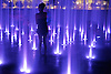 Young woman among glowing water jets at night in a fountain at Butler Park in Austin, Texas, USA.