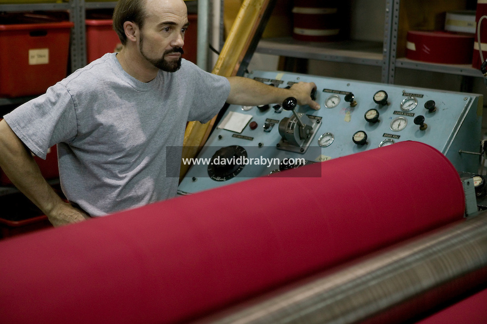 21 June 2005 - Oaks, PA - A worker re-rolls polyester fabric that will be turned into red stripes at the Annin & Co. American flag manufacturing plant in Oaks, PA, USA. Photo Credit: David Brabyn.