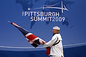Pittsburgh, PA - September 24, 2009 -- A serviceman walks with a flag before the welcoming dinner for G-20 leaders at the Phipps Conservatory on Thursday, September 24, 2009 in Pittsburgh, Pennsylvania. Heads of state from the world's leading economic powers arrived today for the two-day G-20 summit, held at David L. Lawrence Convention Center, aimed at promoting economic growth. .Credit: Win McNamee / Pool via CNP
