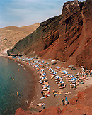 GREECE, Santorini, Akrotiri, people sunbathe and swim at Red Sand Beach, the Mediterranean Sea