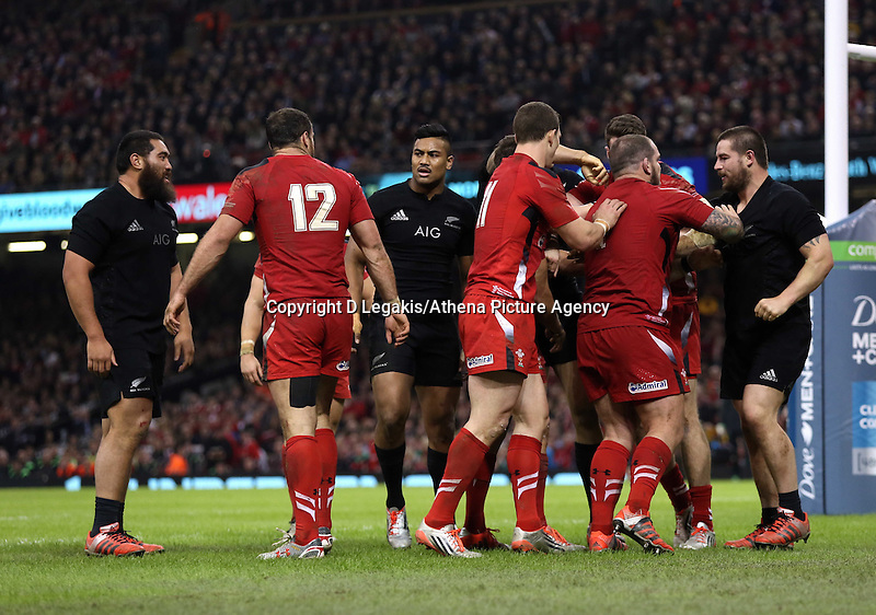 Pictured: A fight breaks out between Dane Coles (R) of New Zealand and Wales players Saturday 22 November 2014<br /> Re: Dove Men Series 2014 rugby, Wales v New Zealand at the Millennium Stadium, Cardiff, south Wales, UK.