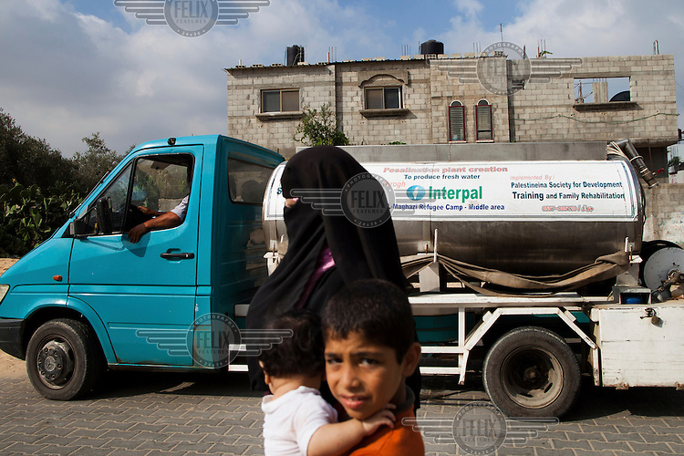 A woman and her children walk past a water truck delivering supplies in the Al-Maghazi refugee camp. The Al-Maghazi Desalination Plant provides drinking water free of charge to local hospitals, schools and mosques and members of the community most in need.