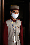 Bellman (bellhop) with SARS mask and thermometer; Broadway Mansion; morning; Shanghai, China, Asia; 050303
