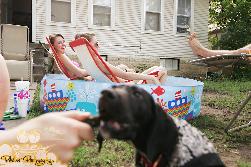 "CHAD PILSTER • Hays Daily News<br /> <br /> (left to right) Fort Hays State University students Dakota Thomas, from Garden City, plays with his dog Ranger, a 10 week labrador and pointer, while Ashley Bowles and her sister Lacey Bowles, from Lindsborg, lounge in the pool as A.J. Brown, from Topeka, reads a book on  Monday, June 17, 2013, along West 6th St. in Hays, Kansas. Brown, said a friend and himself bought the pool on a whim one day when they were in WalMart and thought ""We need a pool."""