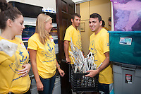 Paul LaGreca, '20, right, moves hangers to a storage room as Gianna Gebhard, '20, left, Emma Sherr,'20 and Steven Croce,'20, help organize at the Seamen's Church Institute during Salve Regina's Exploration Day of Service.