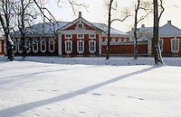 The striking red Neoclassical stables stand out against the snow-covered landscape