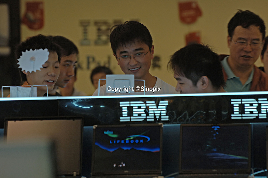 "Consumers browsing IBM laptop computers in a computer plaza in Chengdu, China. Chengdu is the capital of China's most populous province, land-locked Sichuan. The capital city is seeing massive investment of capital as it has modeled itself as the gateway to the western China which the Chinese government are trying to encourage investment with its ""Go West"" campaign.."