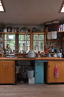 The simple kitchen is furnished with hand-made wooden cupboards and a matching work surface
