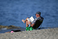 1st April 2020, Kohi Beach, Auckland, New Zealand; A man reading on the beach making the most of the warm weather during the lockdown due to Covid-19. Kohimarama, Auckland, New Zealand on Wednesday 1 April 2020.