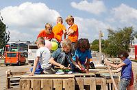 Nederland Amsterdam  2015 06 10 . Landelijke Buitenspeeldag. Honderden kinderen spelen buiten op het NDSM terrein. Jongens bouwen een hut