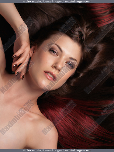Beautiful woman with long brown hair and red hair extensions