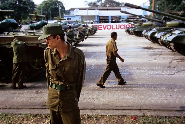 A Cuban Revolutionary Armed Forces (FAR) soldier guards Soviet made tanks the day before a parade marking the 50th anniversary of the landing of Granma and a celebration for Fidel Castro's 80th birthday in Havana, Cuba on 1 December 2006. Castro's original birthday celebration was delayed for three and a half months due to poor health.