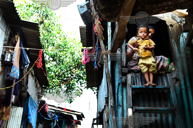 A mother and child in front of their one room slum house in Dharavi, a 175 hectare maze of small alleys sustaining  more than a million residents.