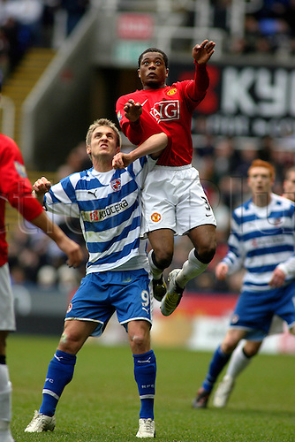 19 January 2008: Man Utd defender Patrice Evra climbs above Kevin Doyle during the Premier League game between Reading and Manchester United played at The Madejski Stadium. Man Utd won the game 0-2. Photo: actionplus...football soccer 080119 player