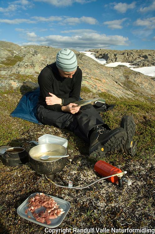 Jente leser kart mens middagen lages: couscous og skinke ---- Girl reading map, while dinner is prepared.