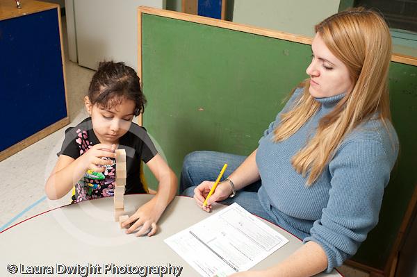 Education preschool 3-4 year olds female teacher administering development assesment psychological test to preschool student girl stacking cubes blocks
