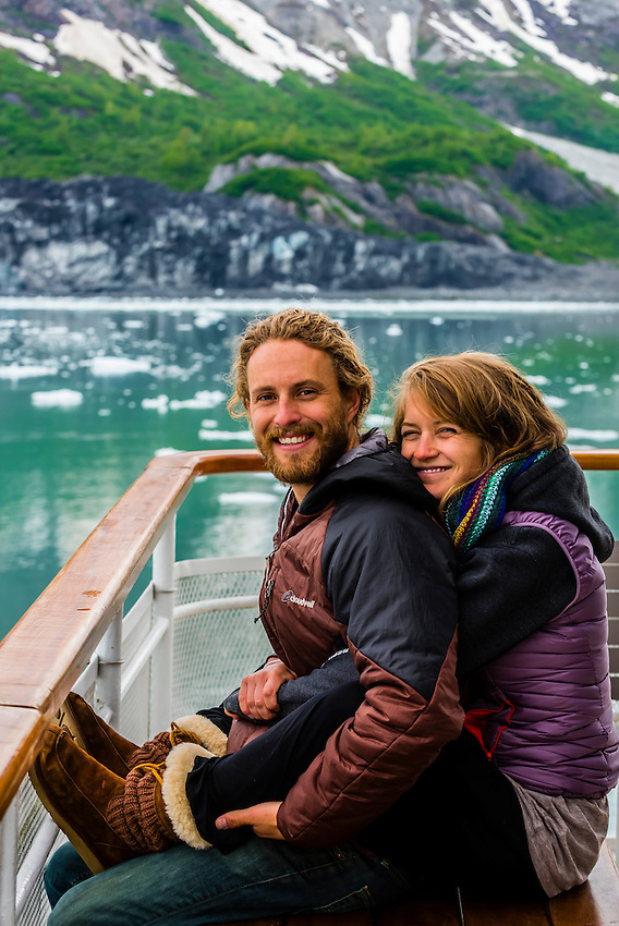 Couple enjoy the scenery of Glacier Bay National Park (Margerie Glacier in background) aboard the Un-Cruise ship Wilderness Explorer, southeast Alaska USA.
