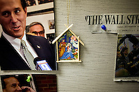 A religious painting hangs among pictures of Rick Santorum and a front page clipping of the Wall Street Journal featuring Santorum at the Rick Santorum New Hampshire campaign headquarters in Bedford, New Hampshire, on Jan. 7, 2012.  Santorum is seeking the 2012 Republican presidential nomination.