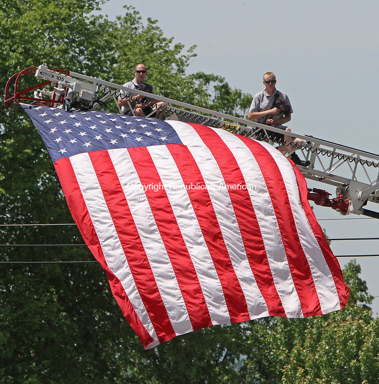 Litchfield, CT-061117MK12 Members of the Litchfield Fire Department honor the U.S. flag during the National Anthem before the 41st Litchfield Hills Road Race Sunday afternoon in Litchfield.  Ngetich won the race with a time of 34 minutes 57 seconds and a 4:56 mile pace. Michael Kabelka Republican-American