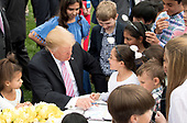United States President Donald J. Trump talks to children as he colors with them during the White House Easter Egg Roll at the White House in Washington, D.C. on April 22, 2019. <br /> Credit: Kevin Dietsch / Pool via CNP