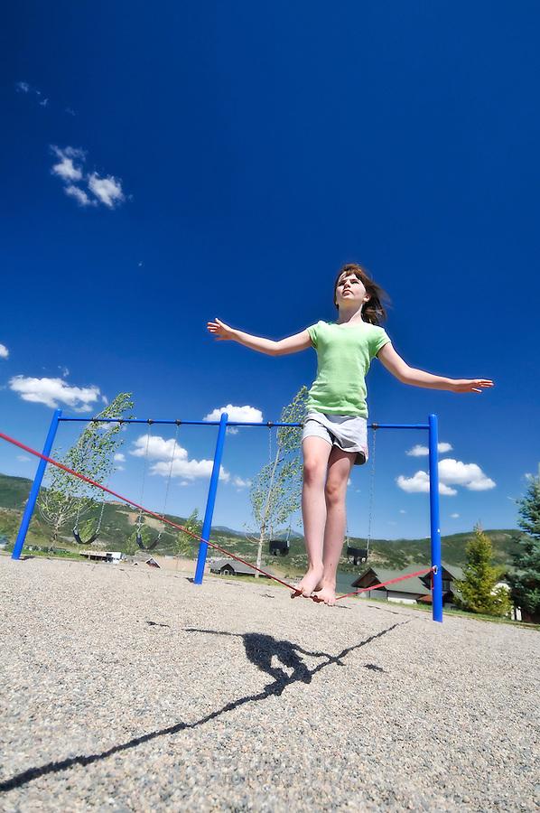 Young girl balancing on slackline on neighborhood playground, Steamboat Springs, Colorado