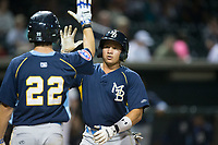 Bryant Flete (right) of the Myrtle Beach Pelicans is greeted at home plate by teammate Daniel Spingola (22) after hitting a home run against the Winston-Salem Dash at BB&T Ballpark on May 11, 2017 in Winston-Salem, North Carolina.  The Pelicans defeated the Dash 9-7.  (Brian Westerholt/Four Seam Images)