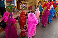 Women in saris walking in a wedding procession, Udaipur, Rajasthan, India