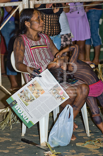 "Altamira, Brazil. ""Xingu Vivo Para Sempre"" protest meeting about the proposed Belo Monte hydroeletric dam and other dams on the Xingu river and its tributaries. Kayapo woman with her daughter holding a printed report from Y Ikatu Xingu."
