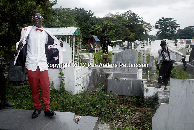 "KINSHASA, DEMOCRATIC REPUBLIC OF CONGO - FEBRUARY 10: Young Sapeurs parade and show their designer label clothes while paying their respect to Stervos Nyarcos, the founder of the kitendi religion, which means clothing in local language Lingala. Nyarcos was known as the leader of the Sape movement, at Gombe cemetery on February 10, 2012 in Kinshasa, DRC. The word Sapeur comes from SAPE, a French acronym for Société des Ambianceurs et Persons Élégants or Society of Revellers and Elegant People and it also means, to dress with elegance and style"". Most of the young Sapeurs are unemployed, poor and live in harsh conditions in Kinshasa,  a city of about 10 million people. For many of them being a Sapeur means they can escape their daily struggles and dress like fashionable Europeans. Many hustle to build up their expensive collections. Most Sapeurs could never afford to visit Paris, and usually relatives send or bring clothes back to Kinshasa. (Photo by Per-Anders Pettersson)"