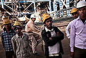 Chinese engineer from Sepco cycles past the Indian workers at the construction site of the Adani Power plant of 4620 MW capacity in Mundra port industrial city of Gujarat, India. Indian power companies have handed out dozens of major contracts to Chinese firms since 2008. Adani Power Ltd have built elaborate Chinatowns to accommodate Chinese workers, complete with Chinese chefs, ping pong tables and Chinese television. Chinese companies now supply equipment for about 25% of the 80,000 megawatts in new capacity.