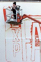 NWA Democrat-Gazette/DAVID GOTTSCHALK  Artist Olivia Trimble continues to paint Friday, June 16, 2017, the logo for Experience Fayetteville on the backside the building on the square in downtown Fayetteville. Experience Fayetteville is the he city's tourism bureau. Trimble hoped to complete the large scale project Friday.
